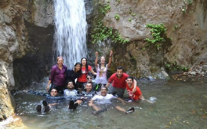 Group of friends taking bath in a waterfall in Rishikesh