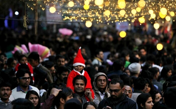 A child sitting on the shoulder of his parents in Janpath Christmas market in Delhi