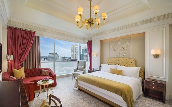 hotel room with chandelier and king size luxurious bed and a glass window
