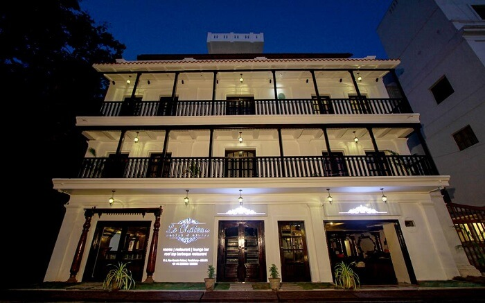 A well lit white traditional hotel building in Pondicherry