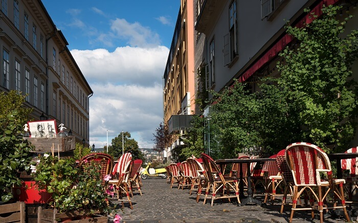 a cafe on street with red and white chairs