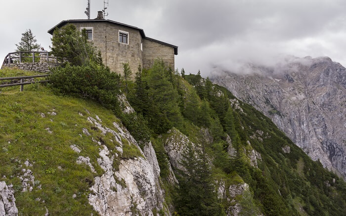 a house at the end of a cliff overlooking mountains