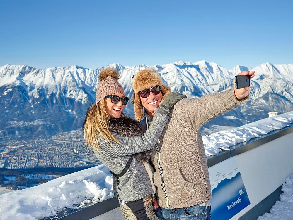 A couple clicking pictures in snow covered innsbruck