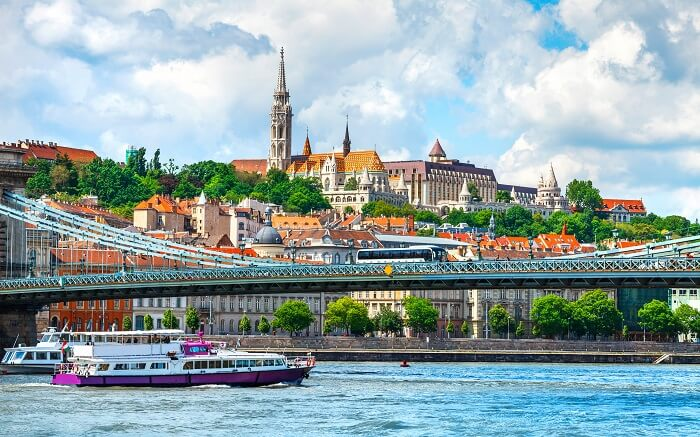 yacht sailing under a bridge with beautiful views