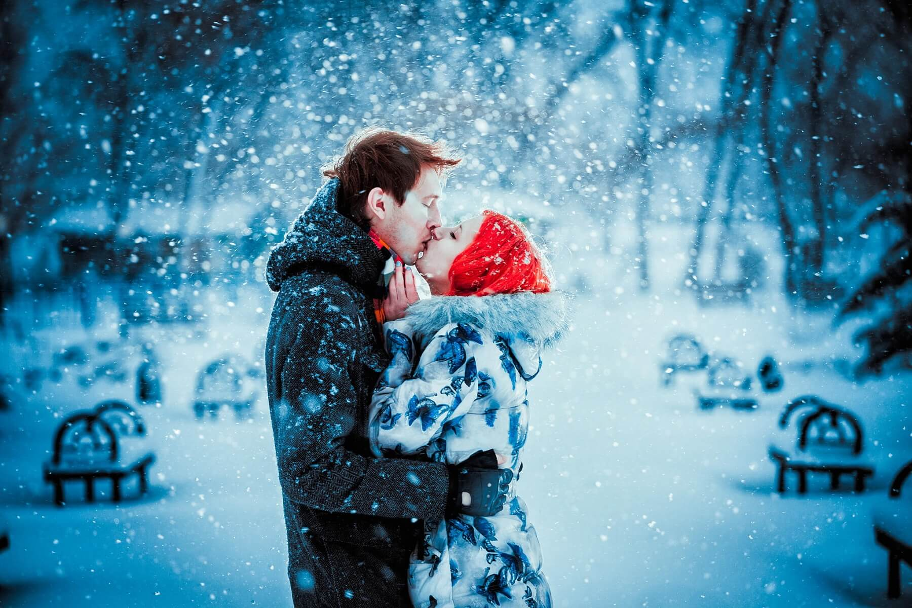 a couple kissing in snowfall