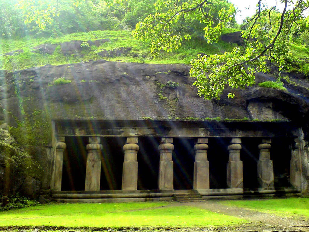 Elephanta caves covered in moss and green trees