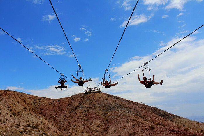 four men zip lining in grand canyon
