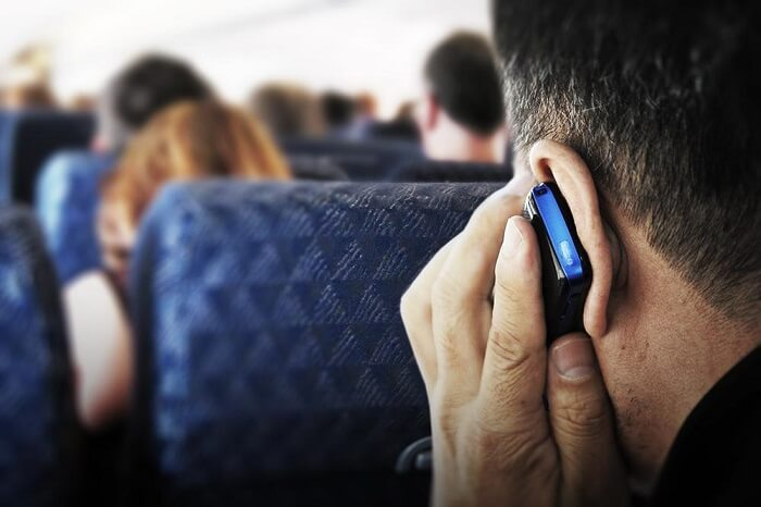 a man taking a call on a flight