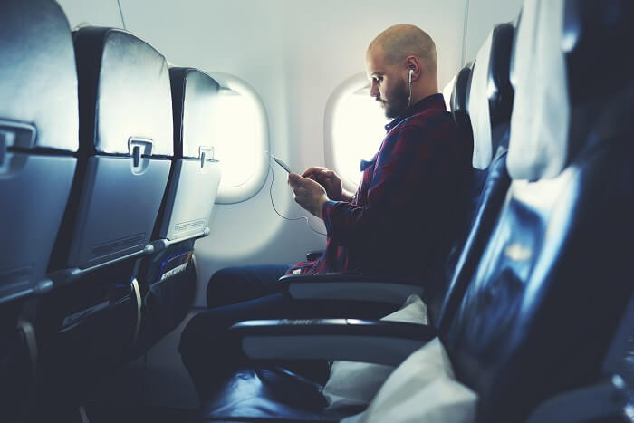 a man listening to music on a flight