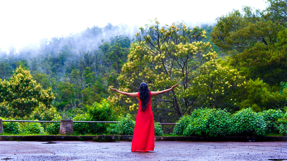 a girl in red dress in mountains