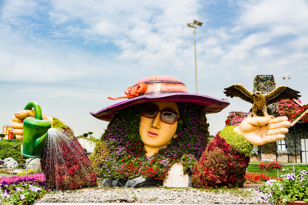 a structure of a lady wearing hat covered by flowers