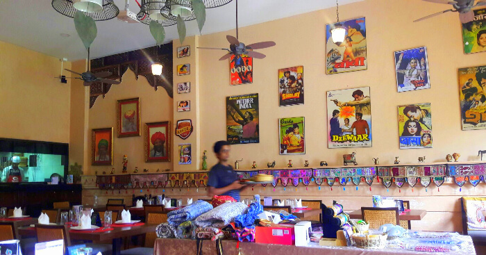 Bollywood theme restaurant with pictures of hindi movies hung on wall