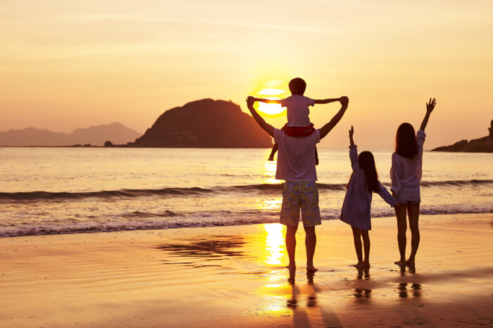 a family on beach during sunset