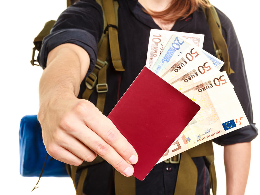 a guy holding euro currency in passport