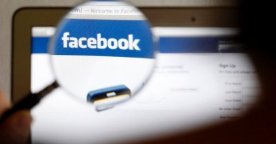 facebook logo seen with a magnifying glass