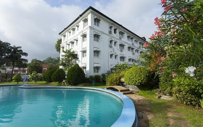 a white painted hotel with an outdoor pool