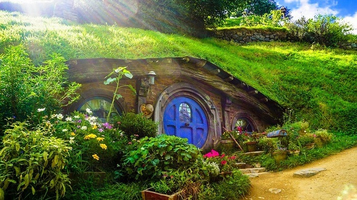 a hobbiton house with blue door