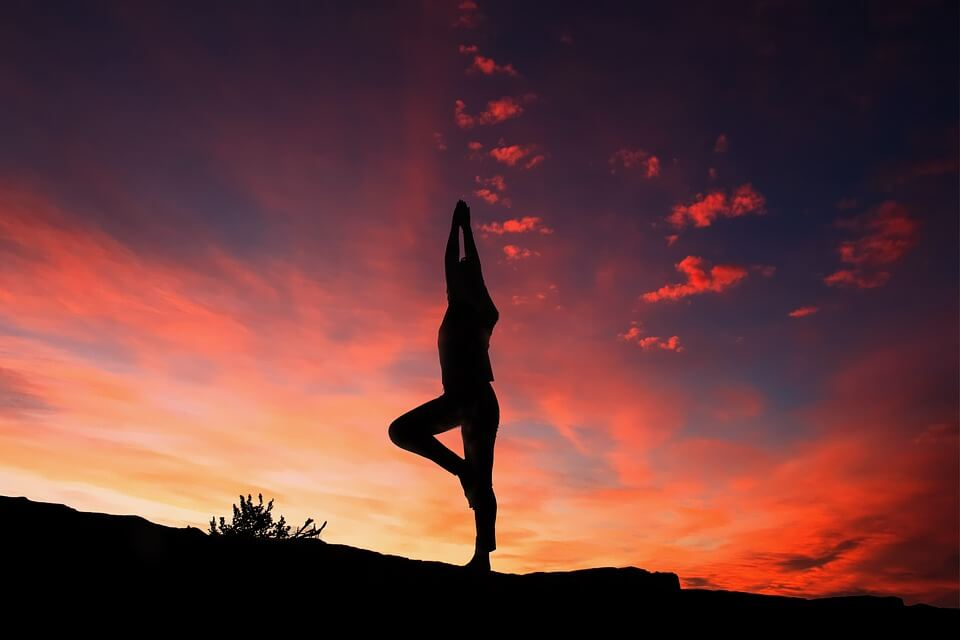 a person doing yoga during sunset