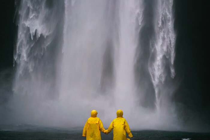 two people standing by a waterfall wearing yellow raincoats