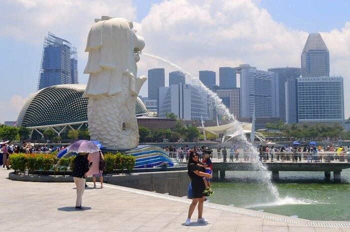 anshu singapore trip: anshu and son posing near merlion