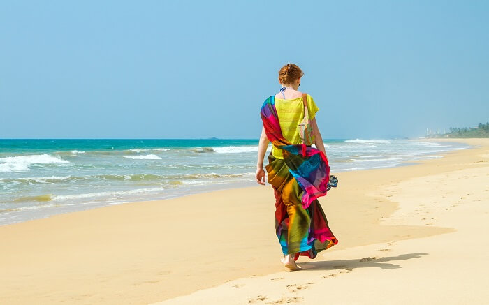 a lady wearing colourful clothes walking on a beach ss01052018