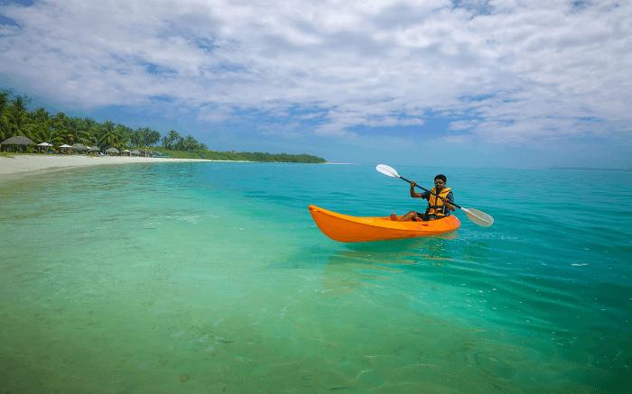 a man kayaking in an orange boat s