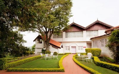 a white beautiful hotel in Coonoor with manicured lawn