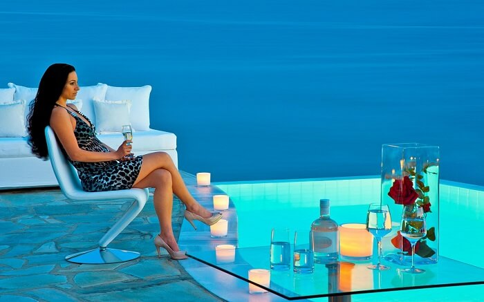 a woman enjoying champagne on the terrace of a resort in Greece