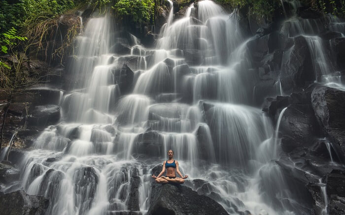 a women doing yoga in front of a waterfall ss11052018
