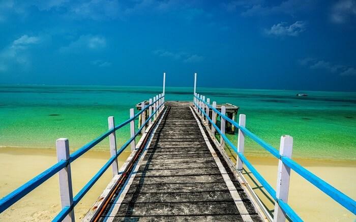 a wooden bridge leading to a beach in Kadmat Island