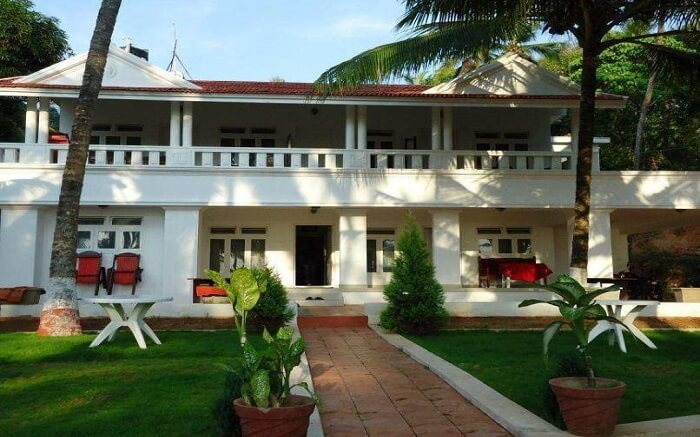 beautiful white Malabar Beach Resort with green lawn