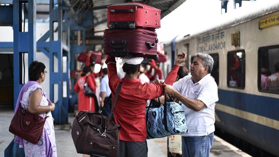 a coolie carrying luggage at a railway station