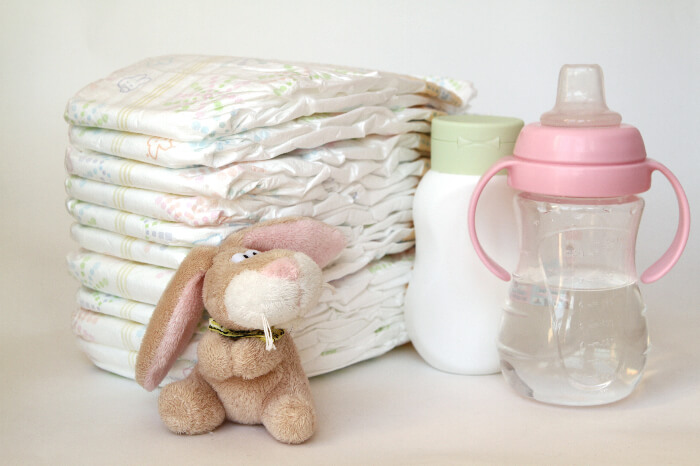 Baby essentials including diapers, water & milk bottles, and a toy
