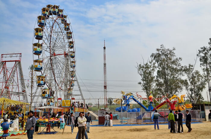 A ferry wheel and other rides in a fair