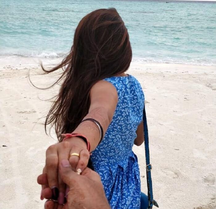 man holding woman's hand on beach