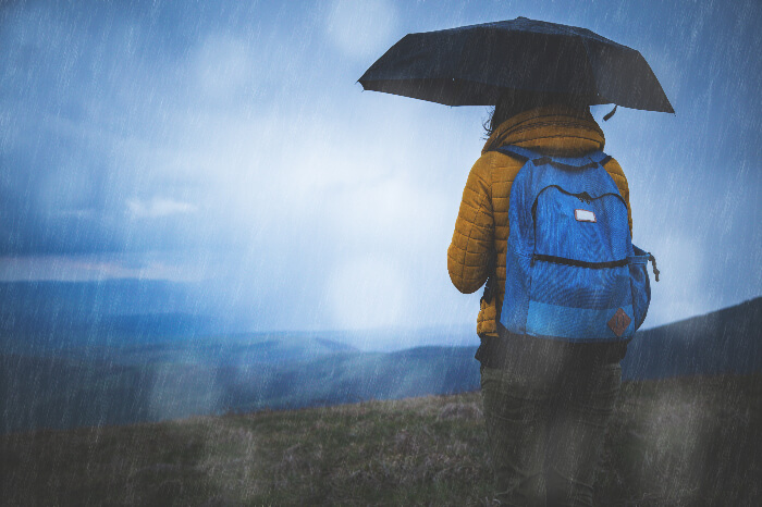 A traveler with a backpack holding an umbrella in the rain on a hill