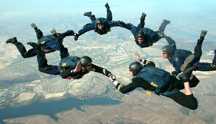 Skydivers holding hands in sky