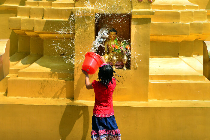 A girl washing the Buddha idol at Namphake Village