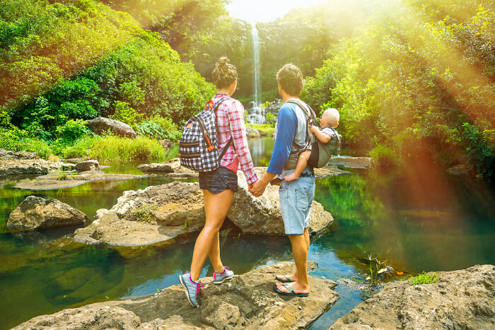 A young couple with their baby, holding hand hand and looking at the waterfall