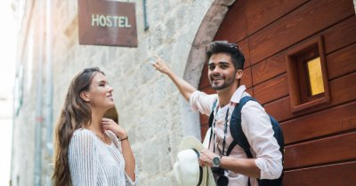 A couple pointing out to a hotel board