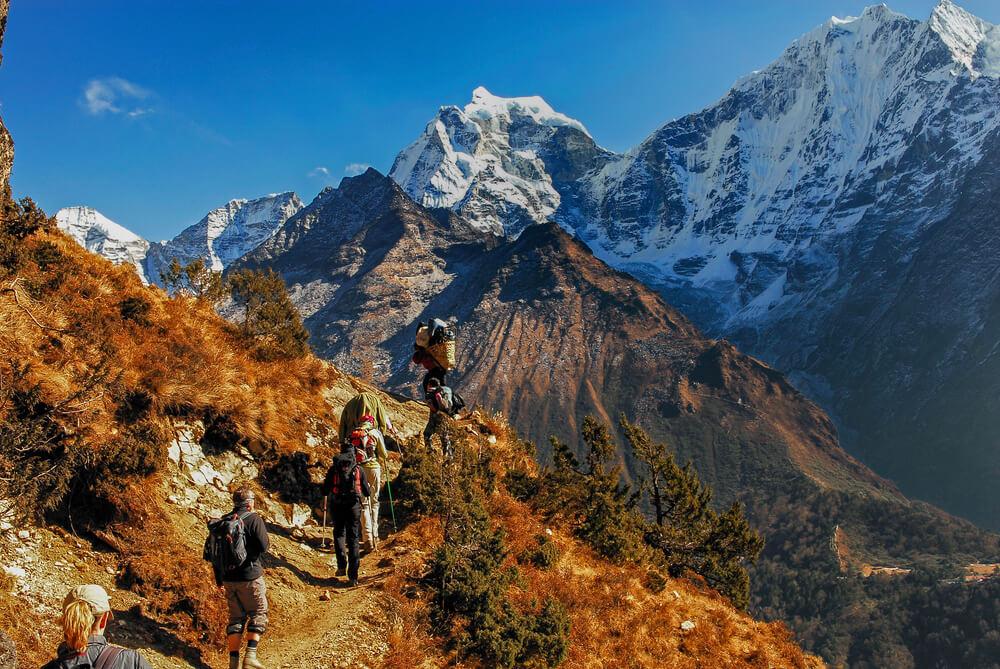 people trekking through mountains