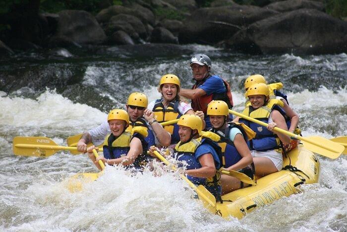 people rafting on a rapid stream