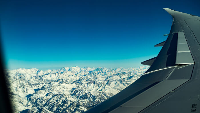 Take A Flight Over Snow Capped Mountains