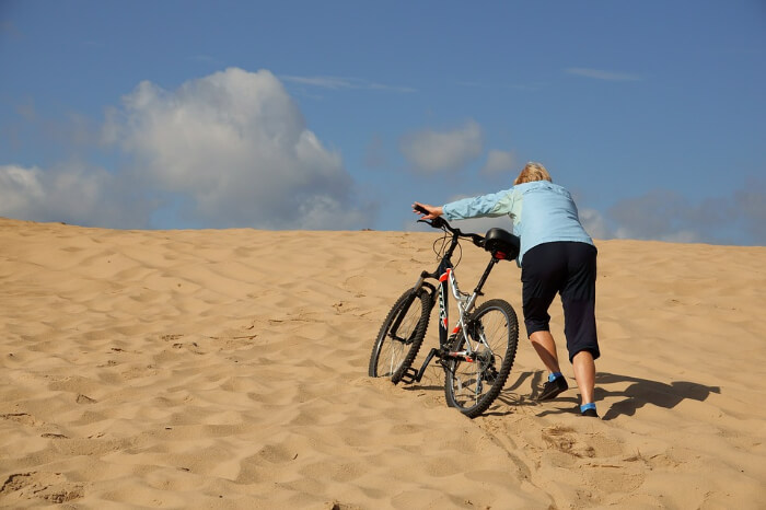 A person hiking the sand dunes with a cycle