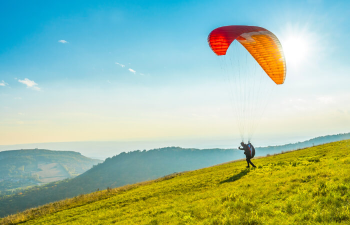 A person ready to paraglide from a hillside
