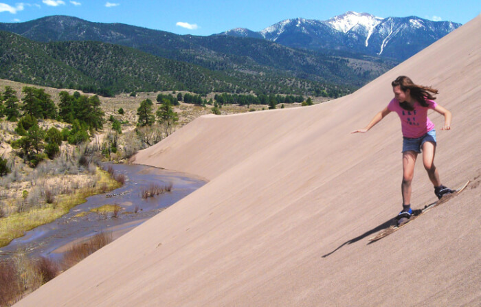 A woman sand-boarding at Great Sand Dunes National Park