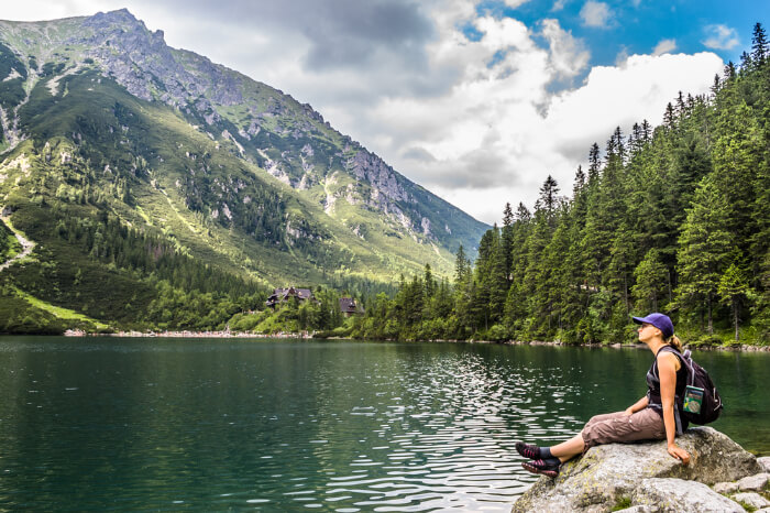 A backpacker sitting on a rock near a Poland lake