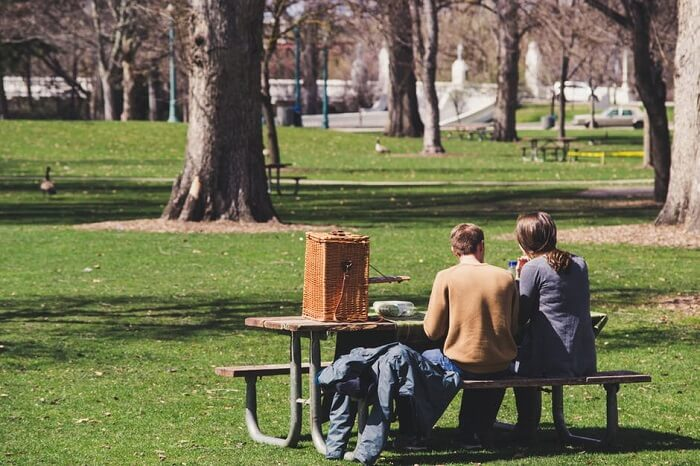 couple sitting in a park bench for picnic