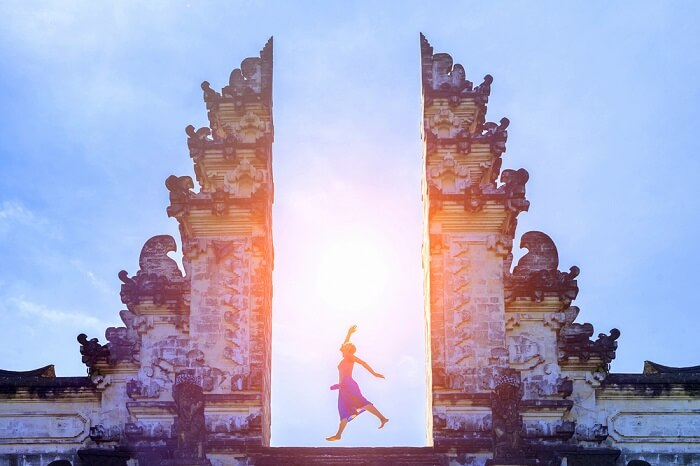 Girl posing at the gate of temple of Bali