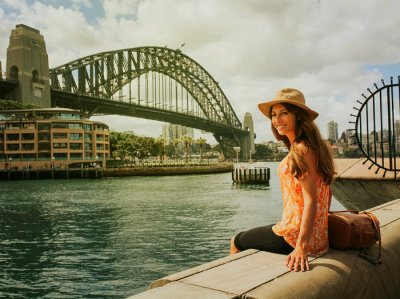 Girl sitting in front of harbour bridge